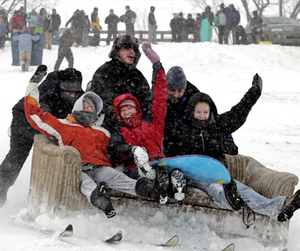 students sledding with a couch